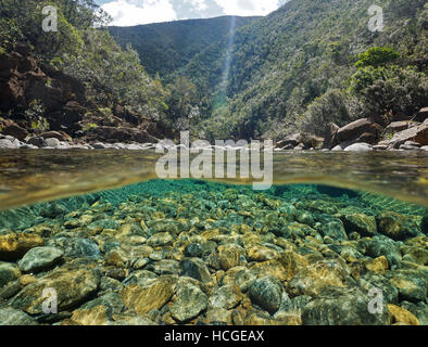 River above and below water surface with rocks on the riverbed underwater, Dumbea river, New Caledonia - Stock Photo