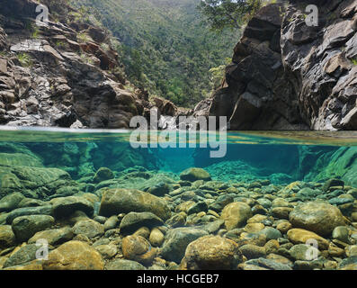 Rocks over and under the water split by waterline in a river with clear water, Dumbea river, New Caledonia - Stock Photo