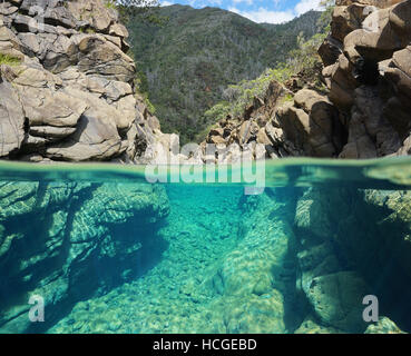 Rocks over and underwater split view in the river Dumbea, New Caledonia - Stock Photo