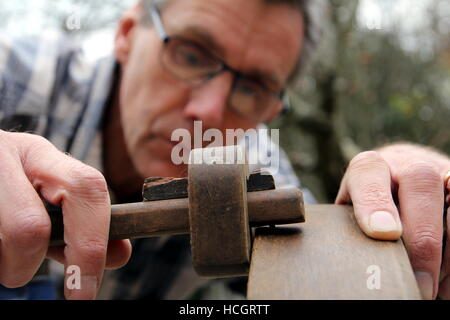 Traditional woodworker using antique brass and wood mortise gauge - Stock Photo