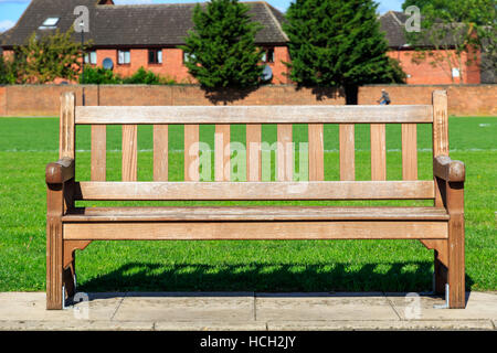 Public wooden bench in a park - Stock Photo
