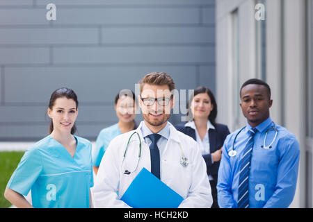 Team of doctors standing together in hospital premises - Stock Photo