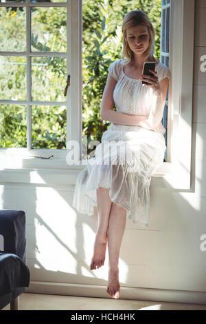 Beautiful woman sitting on windowsill and using mobile phone - Stock Photo