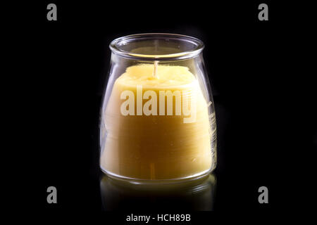 Beeswax candle (unlit) in a glass jar on a black background with a subtle reflection - Stock Photo