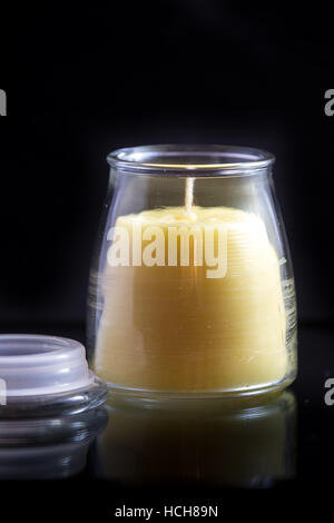 Beeswax candle (unlit) in a glass jar on a black background with a subtle reflection and a lid. - Stock Photo