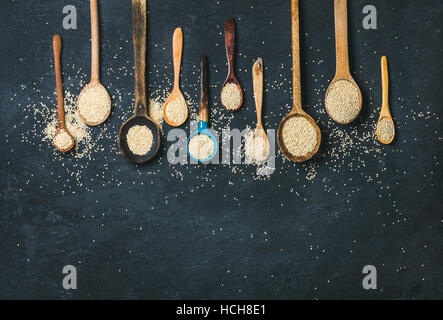 Quinoa seeds in different spoons over black stone background, top view, copy space. Superfood, healthy eating, dieting, - Stock Photo