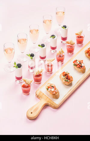 Catering, banquet or party food concept. Various snacks, brushetta sandwiches, gazpacho shots, desserts with berries - Stock Photo