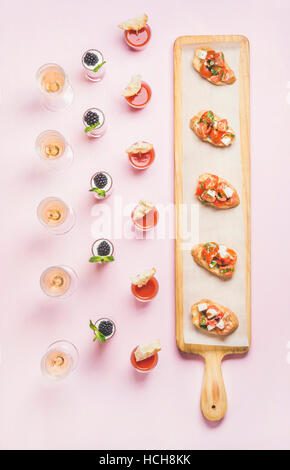 Catering, banquet food concept. Various snacks, brushetta sandwiches, gazpacho shots, desserts with berries on corporate - Stock Photo