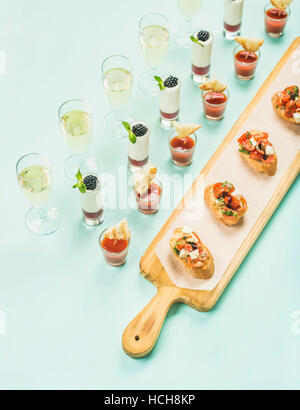 Various snacks, brushetta sandwiches, gazpacho shots, desserts with berries and champagne on corporate event, christmas, - Stock Photo