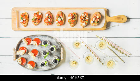Brushetta sandwiches with tomatoes, gazpacho shots, desserts with berries and champagne in glasses, straws on corporate - Stock Photo