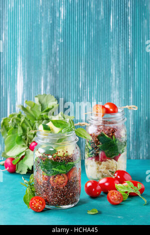 Salads with quinoa, couscous, spinach, radish, tomatoes and zucchini in glass mason jars, standing with fresh vegetables - Stock Photo