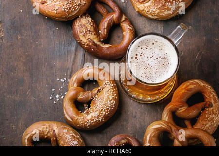 Glass of lager beer with traditional salted pretzels over old dark wooden background. Top view with space for text. - Stock Photo