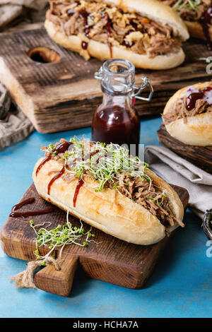 Variety of pulled pork sandwiches with meat, fried onion, green sprouts and bbq ketchup, served on wood cutting - Stock Photo
