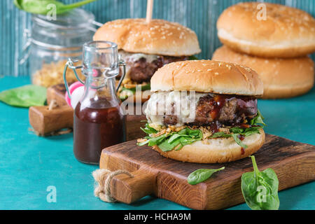 Two hamburgers with beef burger cutlet, fried onion, spinach, ketchup sauce and blue cheese in traditional buns, - Stock Photo