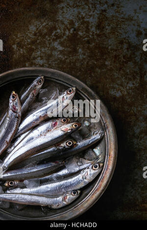 Lot of raw fresh anchovies fishes on crushed ice in vintage plate over old dark metal background. Top view. Sea - Stock Photo