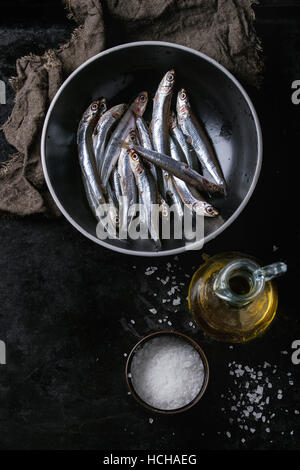 Lot of raw fresh anchovies fishes in black ceramic bowl with sea salt and bottle of olive oil for marinade over - Stock Photo