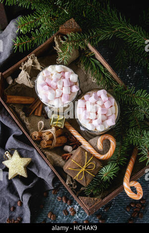 Two glasses of cafe latte with pink marshmallow standing in wooden box with Christmas decor, candies, spices, coffee - Stock Photo