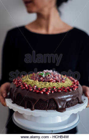 A woman holding a Christmas Chocolate Cake decorated with pomegranate seeds and ground pistachio. - Stock Photo