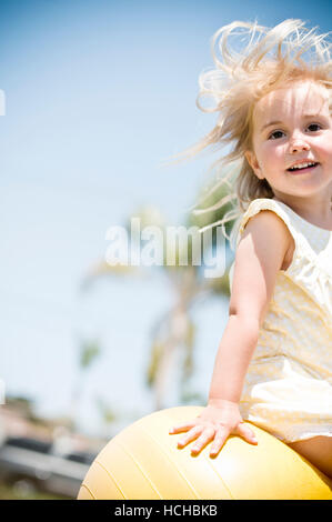 A young girl having fun bouncing outside on a bright yellow ball. - Stock Photo