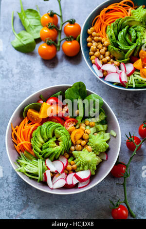 Buddha vegetable bowl with avocado, romanesco cauliflower, carrots, chickpeas, tomatoes and radishes - Stock Photo