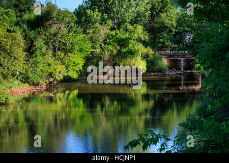 An old bridge covered in trees by a lake shore. - Stock Photo