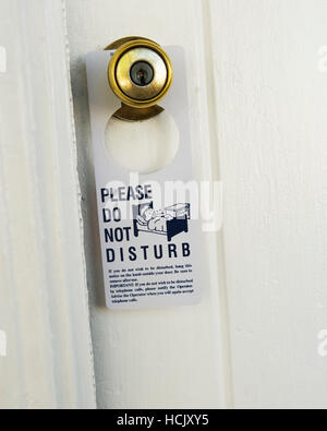 A 'Please Do Not Disturb' sign hanging on a motel doorknob. - Stock Photo