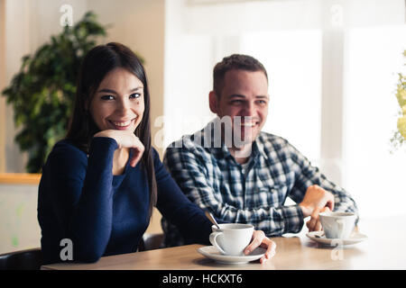 Young couple talking in coffee shop - Stock Photo