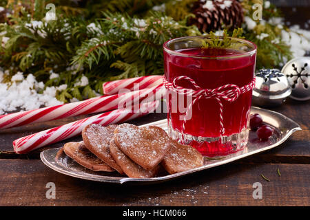 Glass of cranberry fruit drink and ginger cookies on metal plate over old wooden table. - Stock Photo