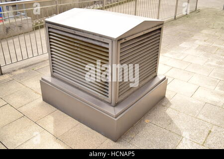 Large silver outdoor air vent on the pavement in a busy city district - Stock Photo