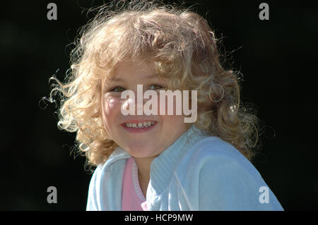 5-year-old laughing girl, with blond hair, backlit, portrait - Stock Photo
