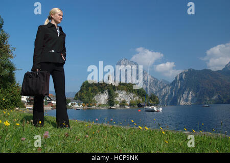 Blonde woman wearing a suit standing by the Traunsee Lake Traunkirchen, Upper Austria, Europe - Stock Photo