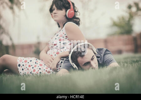Boy and girl  listening to music on headphones - Stock Photo