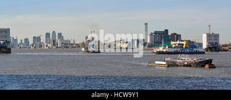 Looking up the River Thames to Woolwich ferry, South East London, UK, Canary Wharf in the distance - Stock Photo