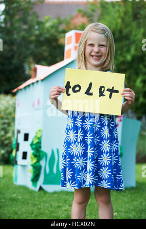 Little Girl Holding To Let Sign Outside Play House - Stock Photo