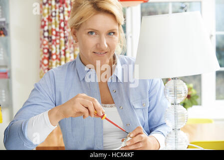 Woman Wiring Electrical Plug On Lamp At Home - Stock Photo
