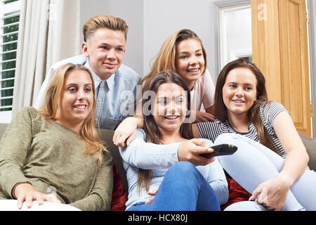 Group Of Teenage Friends Watching Television At Home - Stock Photo