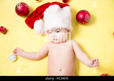 Baby in a red Santa hat with balls on the New year tree. Beautiful little baby celebrates Christmas. - Stock Photo