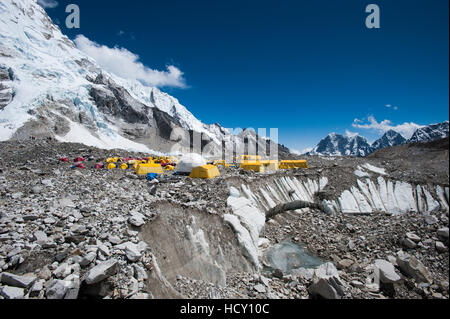 Tents at Everest Base Camp set up on the glacier among the boulders and holes in the ice, Khumbu Region, Nepal - Stock Photo