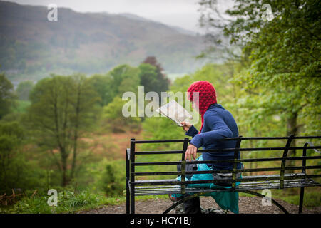 A woman rests on a bench while walking in The Lake District near Grasmere, Cumbria, UK - Stock Photo