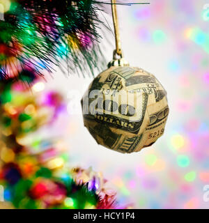 a christmas ball wrapped in pieces of a one hundred dollar banknote hanging from the branch of a christmas tree - Stock Photo
