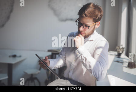 Serious businessman on coffee break using phone - Stock Photo