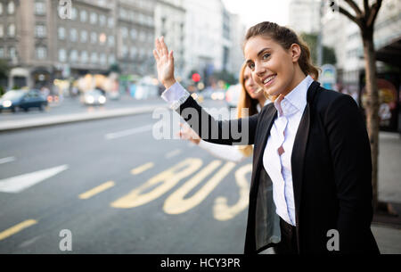 Business women hailing taxi on street - Stock Photo