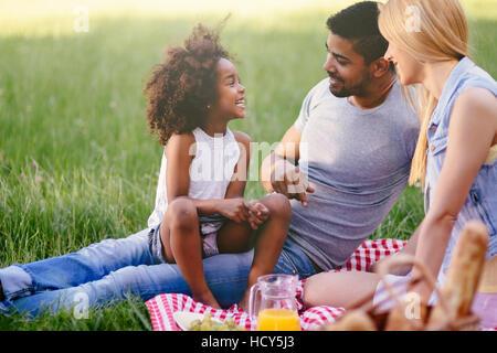 Happy family enjoying picnic in nature - Stock Photo
