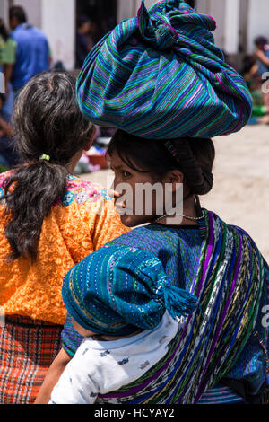 A young Mayan woman in the traditional dress from San Antonio Palopó, Guatemala, carries her baby on her back in - Stock Photo