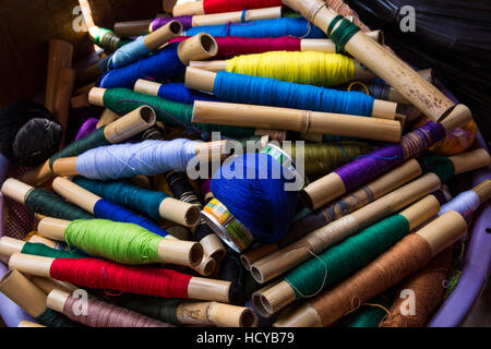 Colorful embroidery thread in a weaving shop in San Antonio Palopó, Guatemala, wound around pieces of bamboo. - Stock Photo