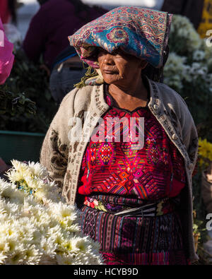 Quiche Mayan woman in traditional dress selling flowers on the steps of the Church of Santo Tomas in Chichicastenango, - Stock Photo
