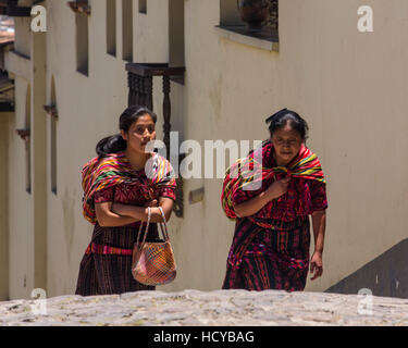 Two Quiche Mayan women, a mother and daughter, in tradtional dress walk up a steep hill in Chichicastenango, Guatemala - Stock Photo