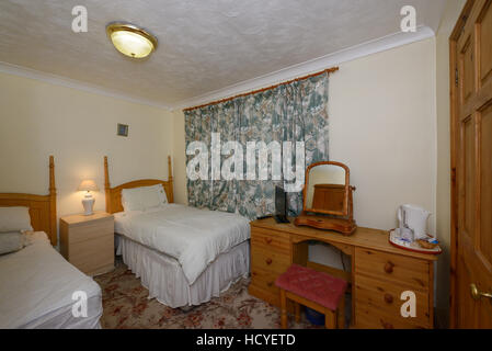 A budget bed and breakfast bedroom in the UK - Stock Photo