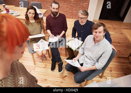 Group of business people listening interesting presentation - Stock Photo