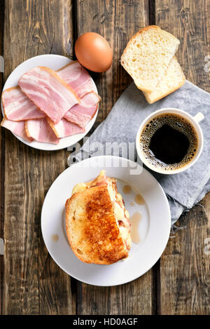Breakfast toast sandwich with cheese, ham and coffee on wooden background, top view - Stock Photo